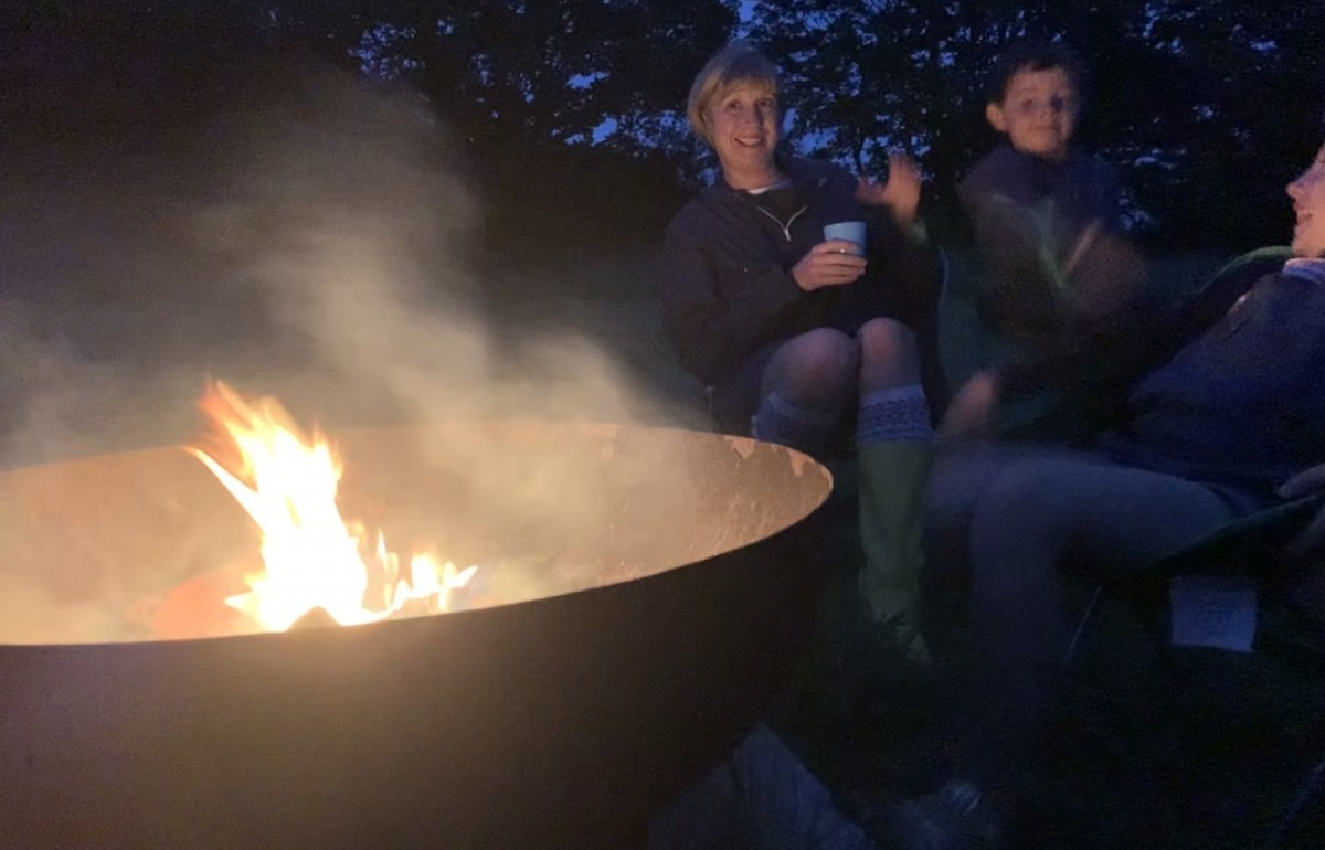 A smiling woman and her young son are seen sitting round a flickering campfire, enjoying a mug of hot chocolate. The smoke rises in the air.