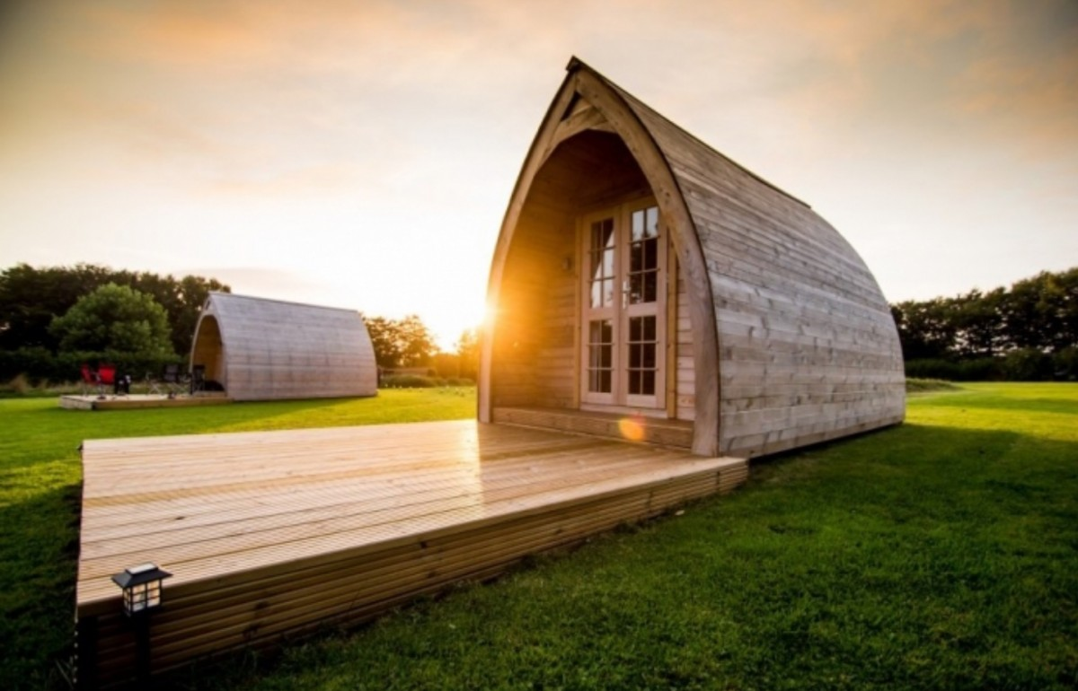 One of the pods at sunset. Decking area in front of the pod doors and the smell of freshly mown grass.