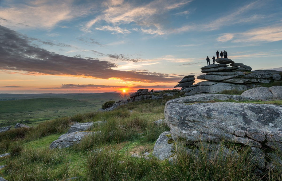 A family silhouetted by the sunset, stand atop Cheeswring Tor.