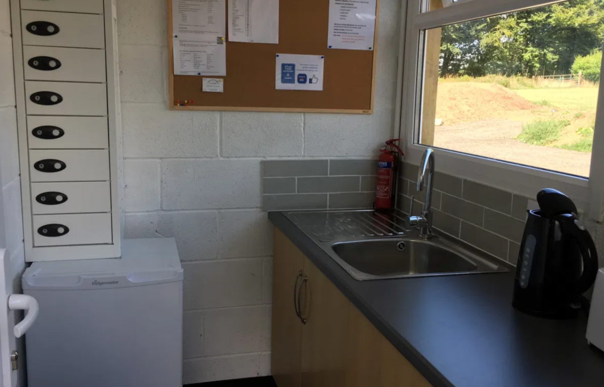 Kitchenette showing fridge, sink, kettle, cupboards and charging lockers