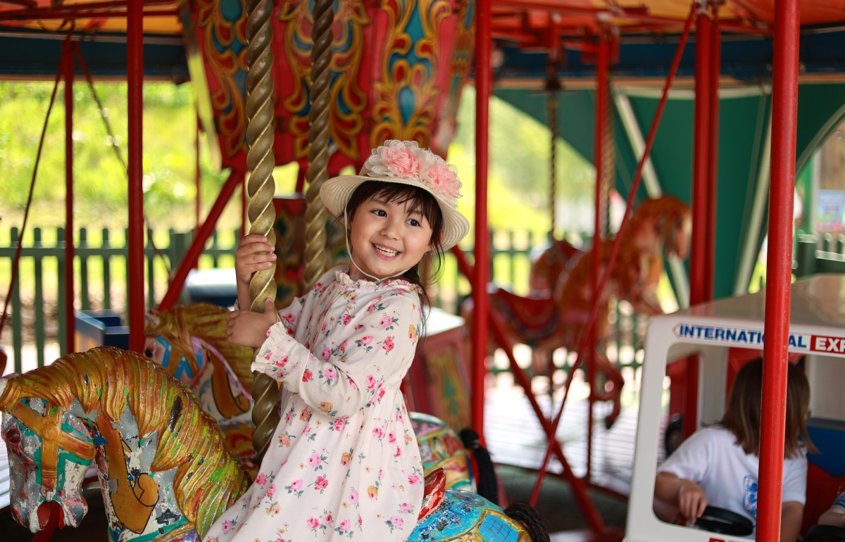 A little girl grinning at camera as she goes around the carousel