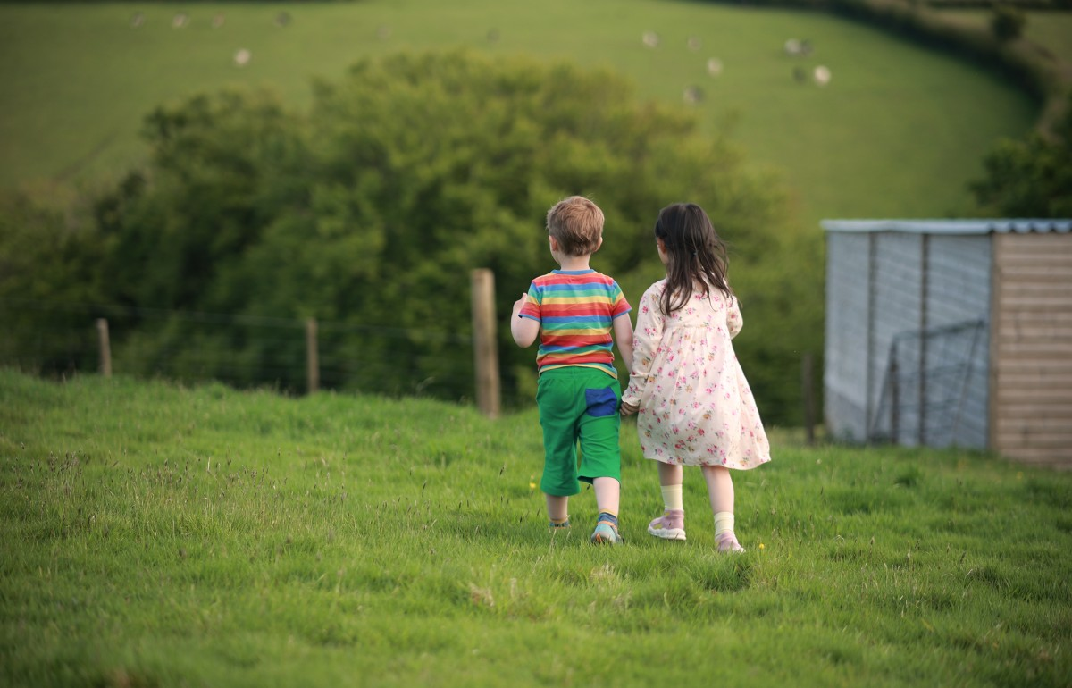 Two young children walk away from the camera in a field