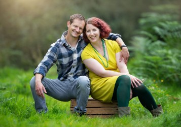 Staged photo of Spencer and India sitting on a wooden box on the grass surrounded by out of focus greenery.